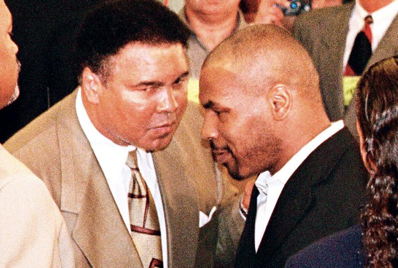 Gegenüber: Tyson (rechts) und Ali schütteln sich die Hände, nach der Entscheidung der Nevada State Athletic Commission, Tysons Boxlizenz 1998 wieder zu erneuern. Alis Frau Lonnie hatte ein vorbereitetes Statement von Ali verlesen, in dem er sich für Tysons Rückkehr in den Boxsport einsetzte.